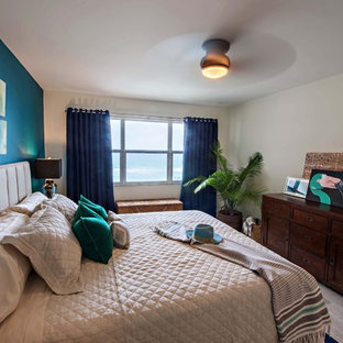 Example of a mid-sized beach style master porcelain tile and gray floor bedroom design in Miami with blue walls