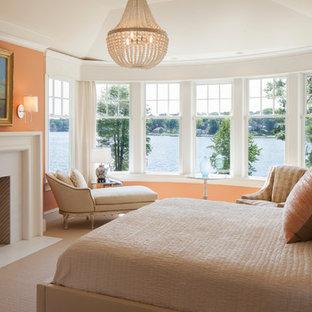 Idee per una camera matrimoniale chic con pareti arancioni, moquette e camino classico