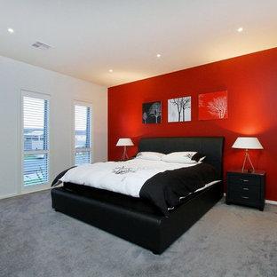 Réalisation d'une grande chambre design avec un mur rouge et un sol gris.