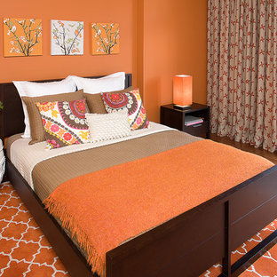 Inspiration for a mid-sized eclectic guest orange floor and medium tone wood floor bedroom remodel in San Francisco with orange walls and no fireplace