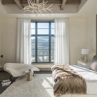 Uriges Hauptschlafzimmer mit beiger Wandfarbe, dunklem Holzboden, Kamin und Kaminumrandung aus Metall in Sonstige