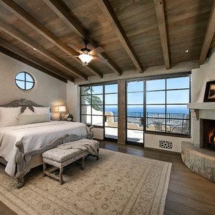 Immagine di una camera da letto mediterranea con pareti bianche, parquet scuro, camino ad angolo, cornice del camino in pietra e pavimento marrone
