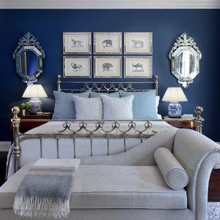 Foto de dormitorio principal, clásico, grande, con paredes azules, suelo de madera en tonos medios, chimenea tradicional, marco de chimenea de piedra y suelo marrón