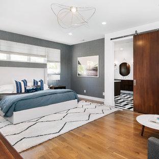 Esempio di una camera matrimoniale minimalista con pareti grigie, pavimento in legno massello medio e nessun camino