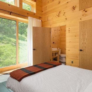 Idee per una camera degli ospiti rustica di medie dimensioni con pavimento in cemento, nessun camino e pavimento nero