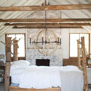 Imagen de dormitorio principal, rústico, grande, con paredes blancas, suelo de madera clara, chimenea tradicional, marco de chimenea de ladrillo y suelo gris