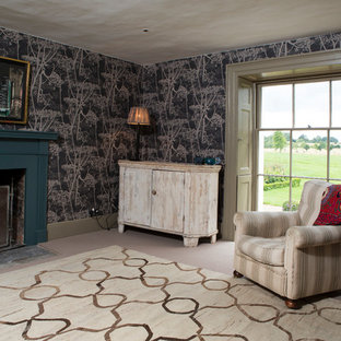 Bedroom - mid-sized country guest carpeted and beige floor bedroom idea in Oxfordshire with black walls and a wood fireplace surround