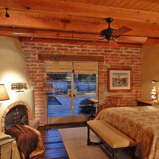 Diseño de dormitorio principal, mediterráneo, de tamaño medio, con paredes beige, suelo de madera oscura y chimenea de esquina