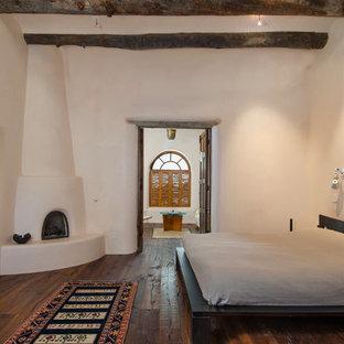 Foto de dormitorio principal, de estilo americano, grande, con paredes blancas, suelo de madera en tonos medios, chimenea de esquina y marco de chimenea de yeso