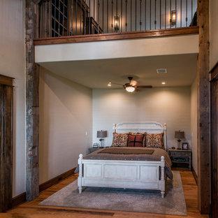 Imagen de habitación de invitados rústica, de tamaño medio, con paredes beige, suelo de madera en tonos medios, chimenea tradicional, marco de chimenea de baldosas y/o azulejos y suelo marrón