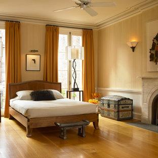 Cette image montre une grand chambre parentale traditionnelle avec un mur beige, un sol en bois brun, une cheminée standard, un manteau de cheminée en pierre et un sol jaune.