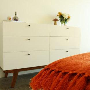 Ejemplo de dormitorio principal, tradicional renovado, de tamaño medio, con paredes blancas, suelo de cemento y suelo beige