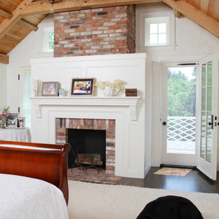 Example of a large farmhouse master carpeted and beige floor bedroom design in Boston with white walls, a standard fireplace and a brick fireplace