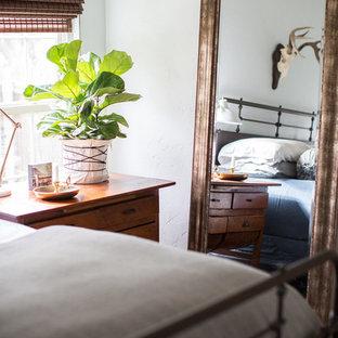 Imagen de dormitorio principal, bohemio, de tamaño medio, sin chimenea, con paredes azules, suelo de bambú y suelo marrón