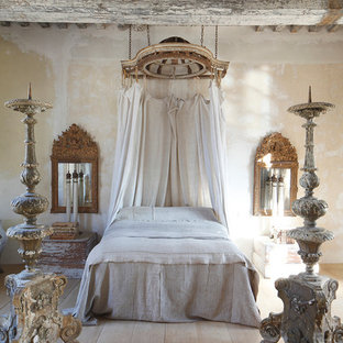 Cette photo montre une chambre parentale chic avec un mur beige, un sol en bois clair et aucune cheminée.