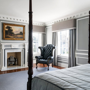 Design ideas for a large traditional master bedroom in Richmond with grey walls, dark hardwood floors, a standard fireplace, a stone fireplace surround and brown floor.