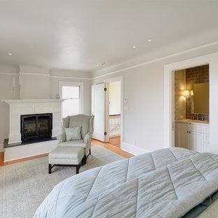 Стильный дизайн: гостевая спальня в стиле ретро с двусторонним камином, серыми стенами, светлым паркетным полом и фасадом камина из штукатурки - последний тренд