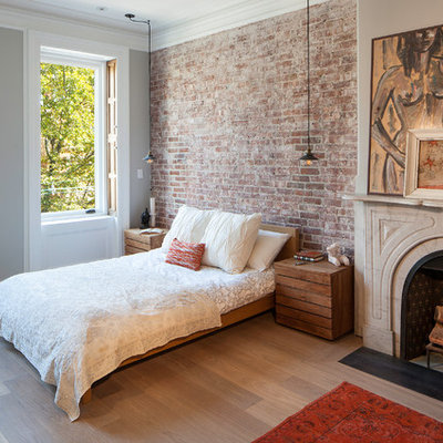 Example of a transitional master light wood floor bedroom design in New York with gray walls and a standard fireplace