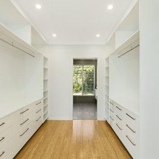 Ejemplo de dormitorio principal, minimalista, de tamaño medio, con paredes blancas y suelo de bambú