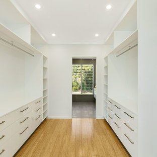 Example of a mid-sized minimalist master bamboo floor bedroom design in Cairns with white walls