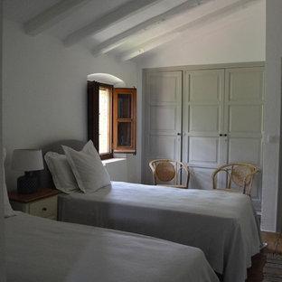 Foto de habitación de invitados rural con paredes blancas y suelo de baldosas de terracota