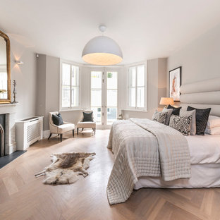 Inspiration for a traditional bedroom in London with beige walls, light hardwood flooring, a standard fireplace and beige floors.