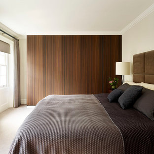 Inspiration for a large contemporary master bedroom in London with beige walls and carpet.