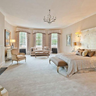 Expansive classic master bedroom in London with beige walls, carpet, a standard fireplace, a metal fireplace surround and beige floors.
