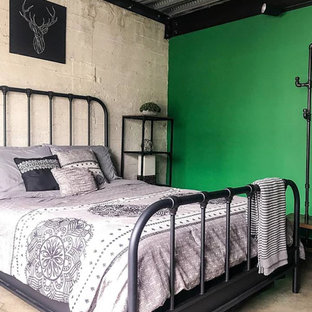 This is an example of a small industrial loft-style bedroom in Los Angeles with green walls, concrete floors and grey floor.