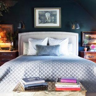 Immagine di una camera da letto chic con pareti nere, pavimento in legno massello medio e nessun camino