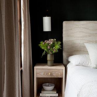 Foto di una camera da letto tradizionale con pareti nere e pavimento in legno massello medio