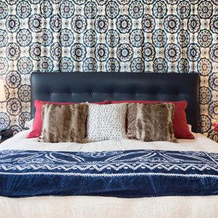 Ejemplo de dormitorio principal, contemporáneo, de tamaño medio, con paredes azules, suelo de madera clara, chimenea de doble cara y marco de chimenea de baldosas y/o azulejos