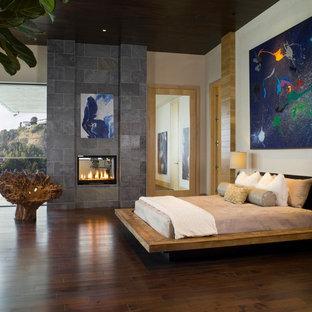 Idee per una camera da letto minimal con pareti beige, parquet scuro e camino bifacciale