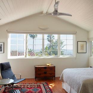 Foto på ett medelhavsstil sovrum, med vita väggar, mellanmörkt trägolv och brunt golv