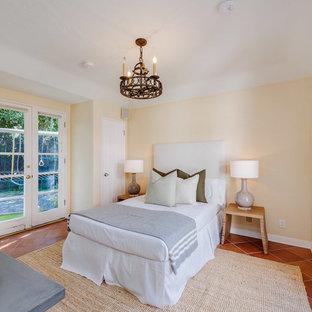 На фото: маленькая гостевая спальня в средиземноморском стиле с бежевыми стенами и полом из терракотовой плитки с