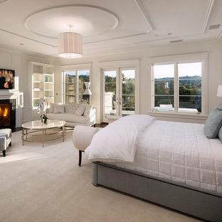 Foto de dormitorio principal, tradicional renovado, extra grande, con paredes blancas, moqueta, chimenea tradicional, marco de chimenea de piedra y suelo blanco