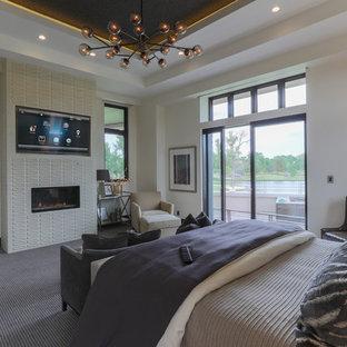 Modelo de dormitorio principal, contemporáneo, grande, con paredes blancas, moqueta, chimenea lineal, marco de chimenea de baldosas y/o azulejos y suelo gris