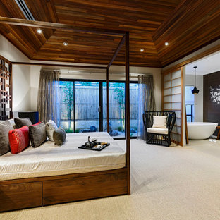 This is an example of a large asian master bedroom in Perth with beige walls, carpet and no fireplace.