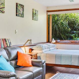 Tropical bedroom in Gold Coast - Tweed with white walls, medium hardwood floors and brown floor.