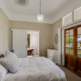 This is an example of a traditional bedroom in Other with beige walls, carpet and brown floor.