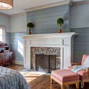 Ispirazione per una camera matrimoniale stile marino di medie dimensioni con pareti blu, parquet scuro, camino classico e cornice del camino in pietra