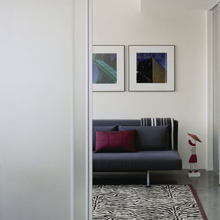 Example of a minimalist concrete floor bedroom design in Boston with white walls