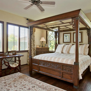 Design ideas for a mid-sized mediterranean master bedroom in San Diego with yellow walls, dark hardwood floors, no fireplace and brown floor.