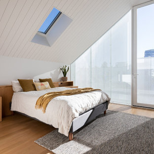 Small contemporary master bedroom in Melbourne with white walls, light hardwood floors and brown floor.