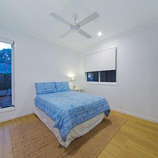 Imagen de habitación de invitados moderna, de tamaño medio, con paredes blancas, suelo de madera clara y suelo verde