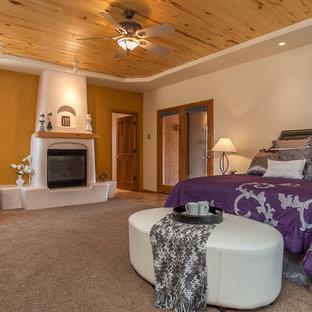 Foto de dormitorio principal, de estilo americano, grande, con paredes amarillas, moqueta, chimenea tradicional y marco de chimenea de yeso