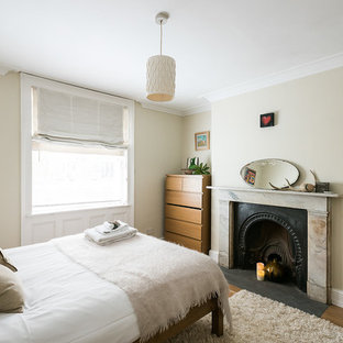 Design ideas for a contemporary bedroom in London with beige walls, medium hardwood flooring and a standard fireplace.