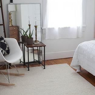 Foto di una piccola camera matrimoniale bohémian con pareti bianche, pavimento in legno massello medio e nessun camino