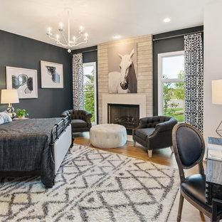Imagen de habitación de invitados de estilo americano, grande, con paredes multicolor, suelo de madera clara, chimenea tradicional y marco de chimenea de madera