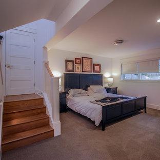 На фото: большая хозяйская спальня в викторианском стиле с белыми стенами, ковровым покрытием, фасадом камина из штукатурки и серым полом с